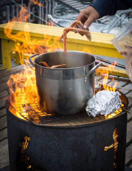 Cooking fresh crab, cod and squid over an open flame in Triton